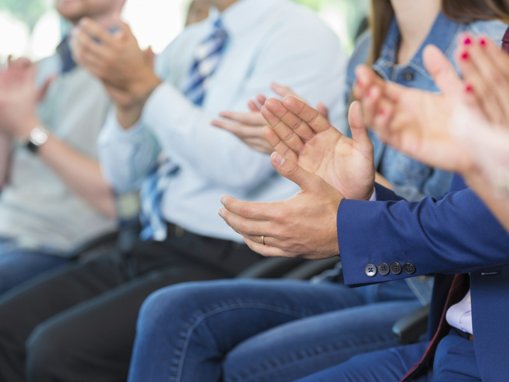 Happy clapping hands. Man in a blue suit in focus. Large group of people in a meeting or classroom.